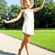 Beautiful young woman with hat in park with big sexy smile — Stock fotografie