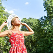 Beautiful young woman with hat in park with big sensual smile — Stock Photo #13289375