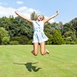 Beautiful young woman jump up to the sky in park — Stock Photo #13289444