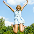 Beautiful young woman jump up to the sky in park — Stock Photo