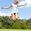 Beautiful young woman jump up to the sky in park in blue dress — Foto de Stock