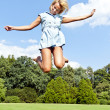Beautiful young woman jump up to the sky in park in blue dress — Стоковая фотография
