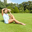 Beautiful young woman in park with big sensual smile on green me — Stock fotografie #13289468