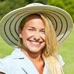 Красивая молодая женщина в шляпе в парке с большой joyfull улыбка — Стоковое фото