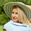 Beautiful young woman with hat in park with big joyfull smile do — Stock Photo #13289499