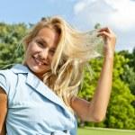 hermosa joven en loawn verde en parque jugando su cabello un — Foto de Stock