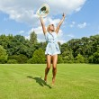 Beautiful young woman jump up to the sky in park in blue dress — Stockfoto