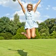 Beautiful young woman jump up to the sky in park in blue dress — Foto Stock
