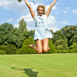 Beautiful young woman jump up to the sky in park in blue dress — ストック写真