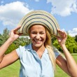 Beautiful young woman with hat in park with big joyfull smile — Stok fotoğraf
