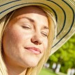 Portrait of beautiful young woman with hat in park with big joyf — Stock Photo