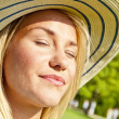Portrait of beautiful young woman with hat in park with big joyf — Stock Photo #13289629
