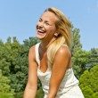 Beautiful young woman in park with big joyfull smile over the sk — Stock Photo