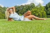 Beautiful young woman in park with big joyfull smile on green me — Stock Photo