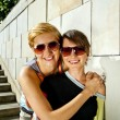 Two beautiful woman with sunglasses on stone wall background — Stock Photo