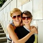 两个漂亮的女人和石头砌的墙背景上的太阳镜 — 图库照片