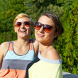 Two beautiful woman with sunglasses on natural background — Stock Photo