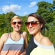 Two  beautiful woman with sunglasses on natural background - Stockfoto