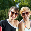 Two  beautiful woman with sunglasses on park - Foto Stock