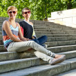 Foto Stock: Two beautiful woman with sunglasses on the stairs