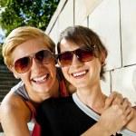 dvě krásná žena s sluneční brýle na pozadí kamená zeď — Stock fotografie