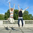 Stock Photo: Beautiful young two girls in jump over the blue sky