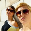 Two  beautiful woman with sunglasses on stone wall background - Foto Stock
