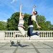 Beautiful young two girls in jump over the blue sky — Foto de Stock