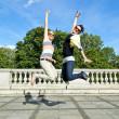krásné mladé dvě dívky v skok přes modré oblohy — Stock fotografie