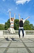 Beautiful young two girls in jump over the blue sky — Stock Photo