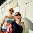 Two  beautiful woman with sunglasses on stone wall background - Zdjęcie stockowe