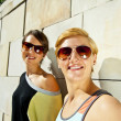 Two  beautiful woman with sunglasses on stone wall background - Photo