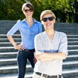 Two  beautiful woman with sunglasses on park - Stock Photo