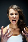 Angry woman on black background — Stock Photo