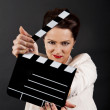 Woman with movie clap over black background — Photo