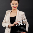 Woman with movie clap over black background — Stock Photo