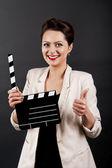 Femme avec film clap sur fond noir — Photo