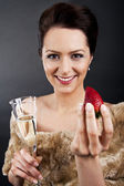 Woman with champagne flute and strawberry — Stock Photo