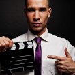 Man with movie clap over dark background — Stock Photo