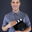 Man with movie clap over dark background — Stok fotoğraf