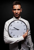 Man with wall clock over dark background — Stok fotoğraf