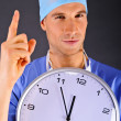 Surgeon with wall clock over dark background — Stock Photo