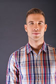 Man overdark background in squared shirt — Stock Photo