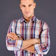 Stock Photo: Man overdark background in squared shirt