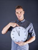 Człowiek posiadający zegar ścienny na ciemnym tle — Zdjęcie stockowe