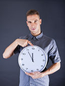 Man holding wall clock over dark background — Stok fotoğraf