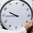 Stock Photo: Man with wall clock over dark background