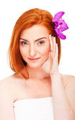 Woman in batrobe with flower in hair — Stock Photo