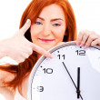 Stock Photo: Young beautiful woman with the clock isolated in white pointing
