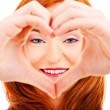 Smiling woman forming a heart with her hands — Stockfoto